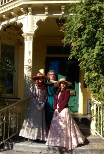Three young women in period dresses and hats stand on the front steps of the Rinckel Mansion.